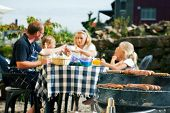 stock photo of bbq party  - Family having a barbecue in the garden - JPG