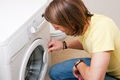 stock photo of washing machine  - Man washing clothes using a washer - JPG