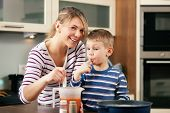image of finger-licking  - Family cooking in their kitchen  - JPG