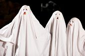 Three very, very scary spooks - kids dressed as ghosts - on Halloween or for carnival or a costume p