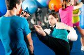 image of sandbag  - Woman Kick boxer kicking her trainer in a sparring session - JPG