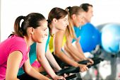 picture of exercise bike  - Group Of Four People In The Gym - JPG