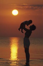 stock photo of children beach  - mother and baby at beach sunset - JPG