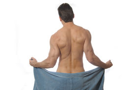 stock photo of denude  - Sexy back of muscular man removing towel - JPG