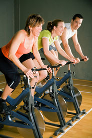 image of fitness man body  - Three People Cycling In A Gym Or Fitness Club - JPG