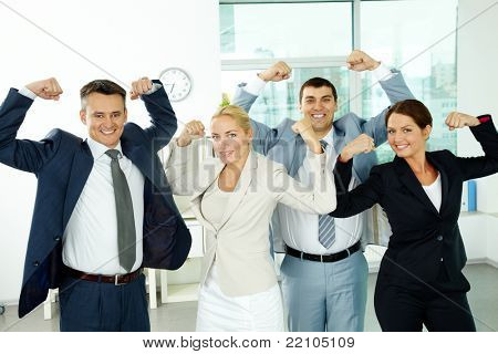 Portrait of business partners posing in front of camera showing their strength