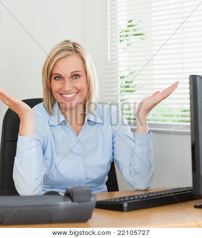Smiling woman sitting behind desk not having a clue what to do next in an office