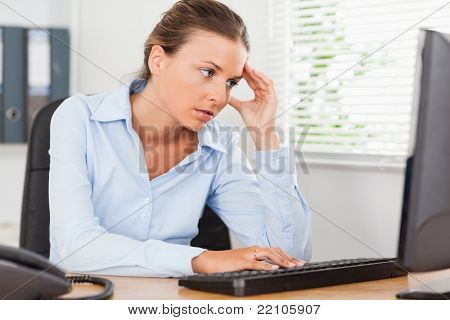 A frustrated businesswoman is looking to the screen of her pc in an office
