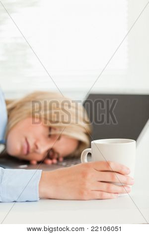 Gorgeous blonde woman sleeping on her laptop holding a cup of coffee in her office