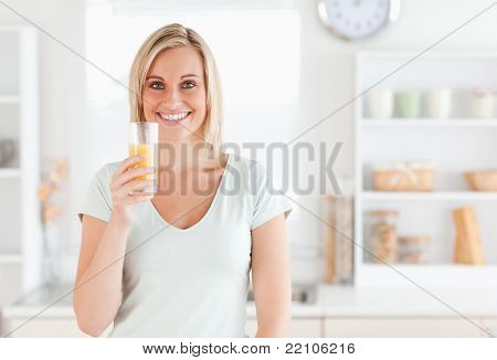 Charming woman holding glass filled with orange juice while standing looking into the camera in the kitchen
