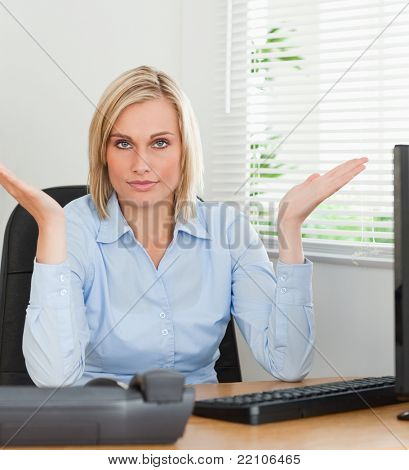 Serious woman sitting behind desk not having a clue what to do next in an office