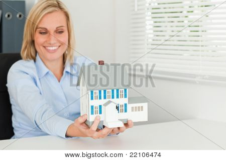 Smiling woman showing model house in her office
