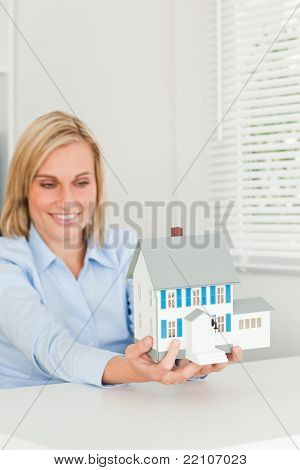 Smiling businesswoman showing model house in her office