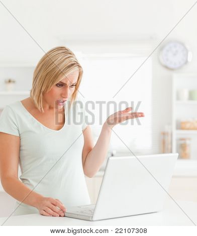 Angry woman looking at notebook in a kitchen without having any clue what to do