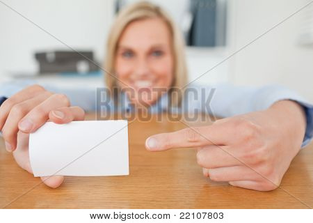 Blonde businesswoman pointing at a card crouching behind her desk in her office