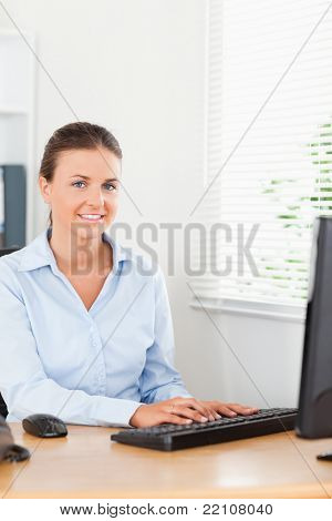A smiling secretary sitting in an office while typing on a keyboard