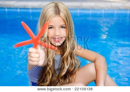 blond girl in summer vacation  pool with starfish