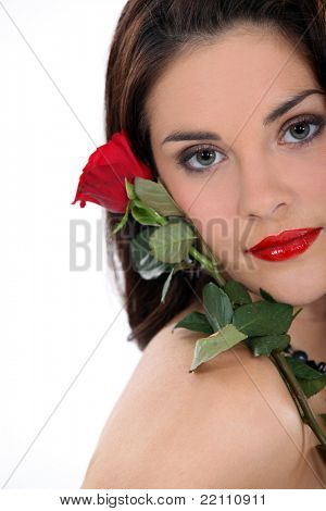 Brunette holding single rose to face