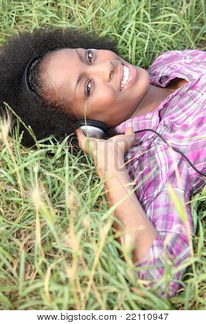 Woman laid in field listening to music