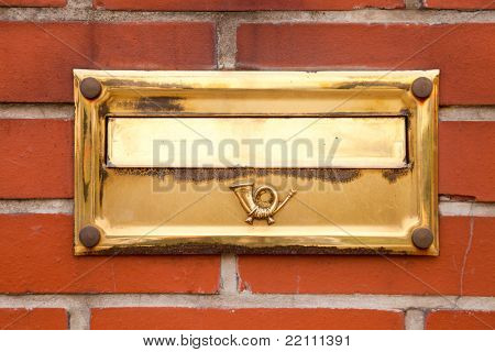 Old gold post box located on brick wall