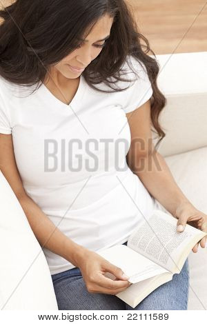 Beautiful happy young Latina Hispanic woman laying down reading a paperback book at home on her sofa