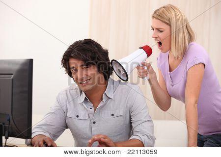 ein Mann tun, Computer und eine Frau schreien auf ihn mit einem Megaphon