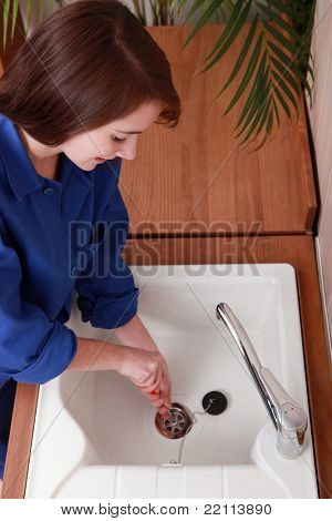 Female plumber installing a sink
