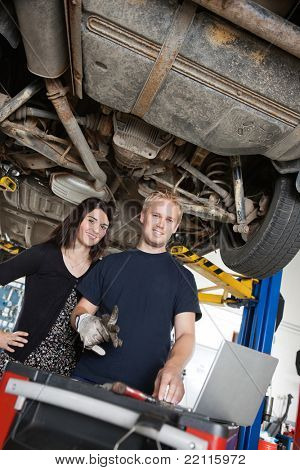 Portrait of young female standing with mechanic using laptop in auto repair shop