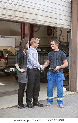 Full length of mechanic shaking hands with client outside garage