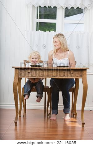 Young woman looking at her cute child at dining table