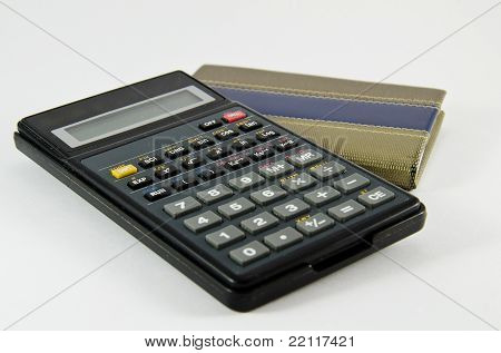 Calculator and a closed notebook isolated on white.