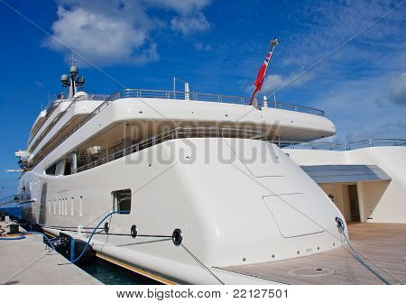 White Yacht At Dock Under Blue Skies