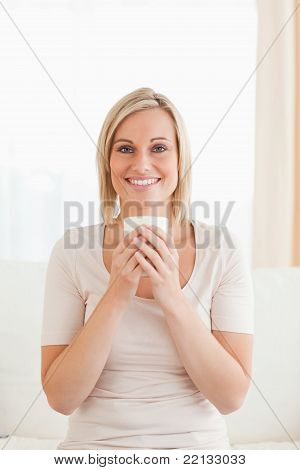 Portrait Of A Smiling Woman Holding A Cup Of Tea
