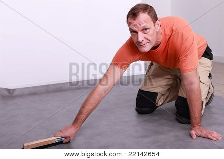 Man smoothing linoleum floor