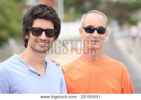 Two men of different generations wearing sunglasses and t-shirts