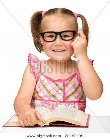 Little Girl Is Flipping Over Pages Of A Book