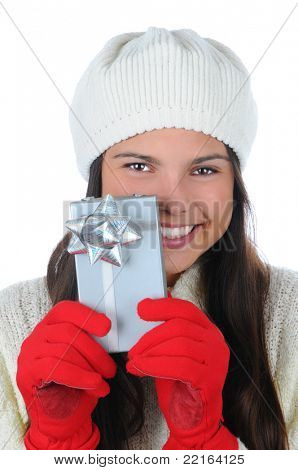 Closeup portrait of an attractive young woman wearing a knit cap holding a small Christmas present in front of her. Vertical format isolated on white.