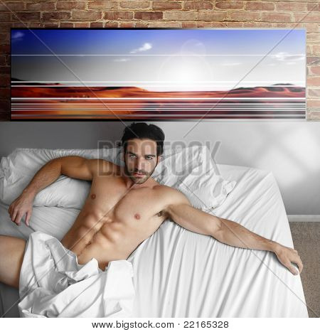 Sexy nude male model laying back in big bed at home in cool loft interior