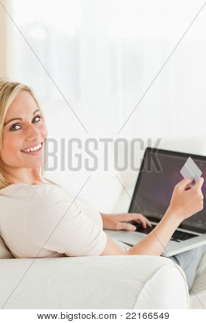 Portrait of a woman paying her bills on line in her living room