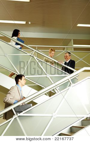 Photo of busy partners communicating while going upstairs in office building