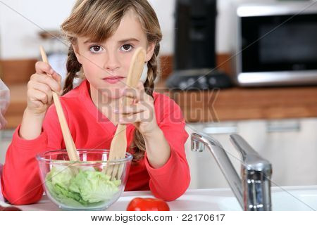 young girl cooking salad