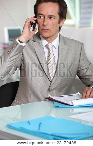 Serious executive taking call on cellphone