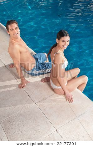 An attractive young smiling couple relaxing by the pool