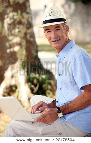 Middle-aged man sat in park with laptop