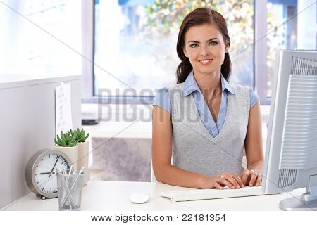Attractive young girl using computer in bright office, smiling.?