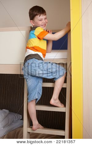 Smiling little boy going up the ladder of bunk bed.?