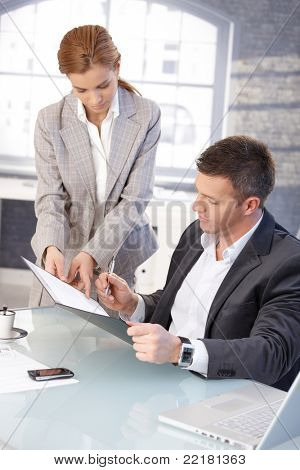 Goodlooking boss signing contract, sitting at desk, secretary showing document.?