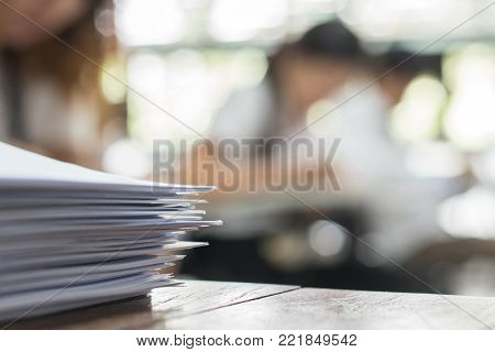 poster of Exam answer sheet or application paper blurry view on table in examination room with blur education background of school university students taking exam test writing answer in seat row with stress