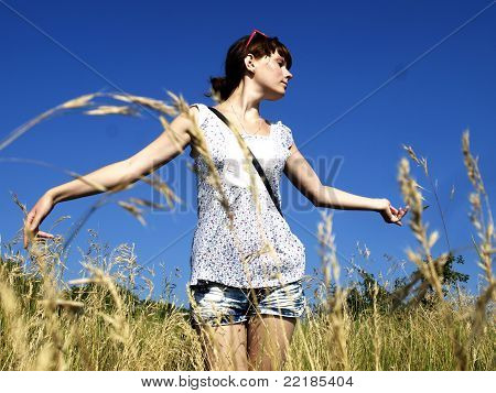 Huge field, the blue sky, hot day and the happy girl