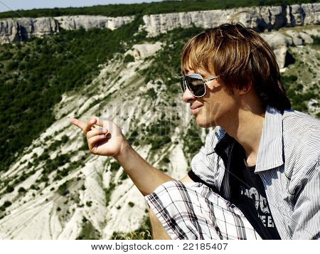 Profile of the young guy wearing spectacles in mountains